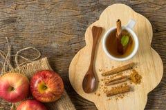 在杯子的顶视图热的苹果汁用在老木头的桂香和肉桂粉 免版税库存照片