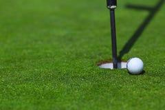 在杯子的嘴唇的高尔夫球 免版税库存照片