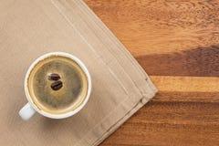 在杯子和二粒豆的黑暗的浓咖啡 免版税库存图片