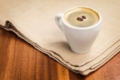 在杯子和二粒豆的黑暗的浓咖啡 免版税库存照片