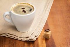 在杯子和二粒豆的黑暗的浓咖啡 库存图片
