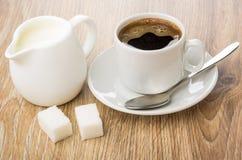 在杯子,水罐的热的咖啡牛奶,糖,匙子 免版税库存照片