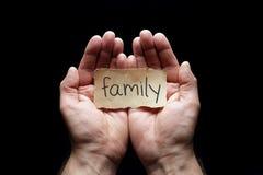 在杯形手上保护的家庭 免版税库存图片