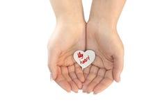 在杯形手上保护的纸心脏 免版税图库摄影