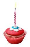 在杯形蛋糕的灼烧的蜡烛 免版税库存图片
