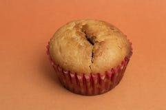 在杯形蛋糕盒的松饼在橙色背景 免版税图库摄影