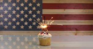 在杯形蛋糕里面的发光的闪烁发光物与美利坚合众国的土气木旗子 股票视频