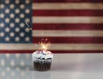 在杯形蛋糕里面的发光的闪烁发光物与Unite土气木旗子  图库摄影