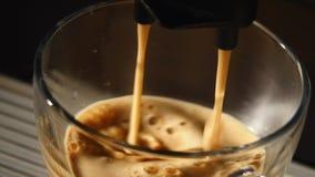 在杯极端特写镜头的咖啡机器倾吐的浓咖啡 库存图片