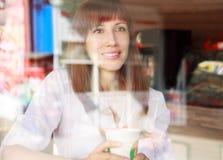 在杯的年轻微笑的妇女咖啡馆后 免版税库存图片