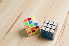 在松木背景的两个rubik立方体  免版税图库摄影