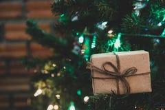 在松树的接近的圣诞礼物箱子有丝带和lightin的 库存照片
