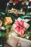 在松树的接近的圣诞礼物箱子有丝带和lightin的 免版税库存照片