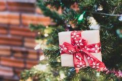 在松树的接近的圣诞礼物箱子有丝带和lightin的 库存图片
