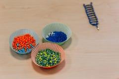 在松饼纸,在制造的镯子的五颜六色的小小珠 库存图片