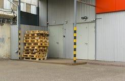 在板台,使用的容器,在仓库前面的门的箱子的看法 免版税库存照片