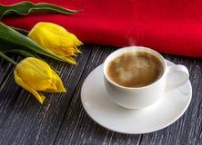 在板和一杯咖啡的黄色郁金香 免版税库存照片