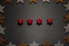 在板岩的四个红色星蜡烛与星框架 免版税库存照片