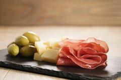 在板岩的Bresaola用帕尔马干酪和橄榄上 库存图片