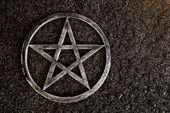 在板岩背景的灰色金属五角星形用水下降 库存照片