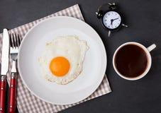 在板材、咖啡和闹钟的煎蛋在黑色 免版税库存照片