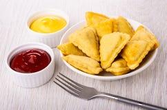 在板材、碗用蛋黄酱和番茄酱,在桌上的叉子的油煎的美味饼 免版税库存照片