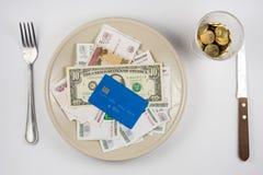 在板材上是很多金钱和塑料信用卡,站立在玻璃和叉子和刀子谎言旁边,顶视图 图库摄影