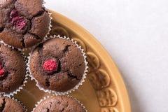 在板材上的平的位置用巧克力杯子蛋糕松饼用莓有白色拷贝空间背景 免版税库存照片