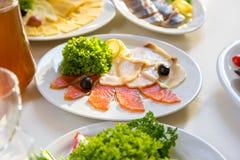 在板材切的红色鱼 被切的红色鱼三文鱼绿化在板材的柠檬黑橄榄 免版税库存照片