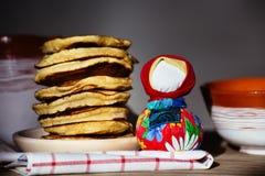 在板材和一个传统民间玩偶的薄煎饼 免版税图库摄影