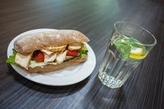 在板材和一杯的三明治在一张桌上的水在咖啡馆 库存照片