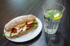 在板材和一杯的三明治在桌上的水 免版税库存照片
