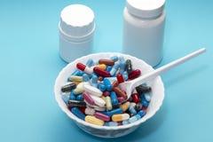 在板材和两白色瓶的不同的药片 免版税图库摄影