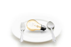 在板材和叉子的在白色隔绝的电灯泡和匙子 免版税库存照片