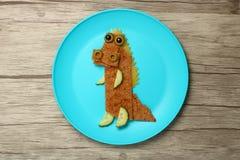 在板材和委员会的滑稽的食物鳄鱼 库存照片