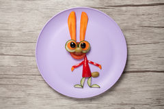 在板材和桌做的滑稽的菜兔子 库存照片