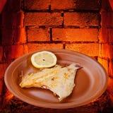 在板材和烤箱热的砖的油煎的单一鱼  库存图片
