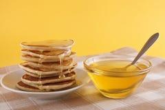 在板材和蜂蜜的油炸馅饼 库存照片