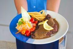 在板材和金黄炸薯条和绿色vege的开胃利益 免版税库存图片