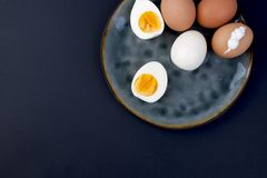 在板材和黑背景的煮沸的鸡蛋 健身食物、蛋白质和卵黄质 文本的自由空间,拷贝空间,平的位置 库存照片