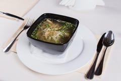 在板材服务的黑碗的开胃汤 库存图片