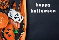 在板材桔子和祝贺的万圣夜曲奇饼 免版税库存图片