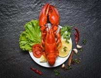 在板材海鲜贝类虾的龙虾与柠檬沙拉莴苣菜和蕃茄 图库摄影
