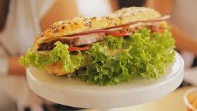 在板材特写镜头的三明治 手扶的射击 三明治用肉,沙拉,乳酪,蕃茄 新鲜和鲜美汉堡包 快速 影视素材