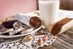 在板材用榛子,在木瓢的可可粉的巧克力香肠 库存照片