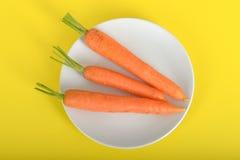 在板材的三棵红萝卜 免版税库存照片