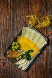 在板材的乳酪盘子在与地方的黑暗的木背景文本的 鲜美的开胃菜 库存图片