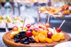 在板材的切的果子,切的果子,葡萄,干果,乳酪,宴会桌,承办酒席,庆祝,新年,圣诞节, foo 免版税库存照片