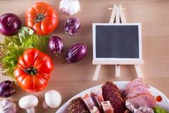 在板材的另外肉开胃菜喜欢jamon、烟肉、蒜味咸腊肠用不同的菜和拷贝空间在黑板 库存图片