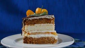 在板材的可口巧克力蛋糕在深蓝背景的桌上 巧克力蛋糕片断与香草奶油的 下落 免版税库存图片